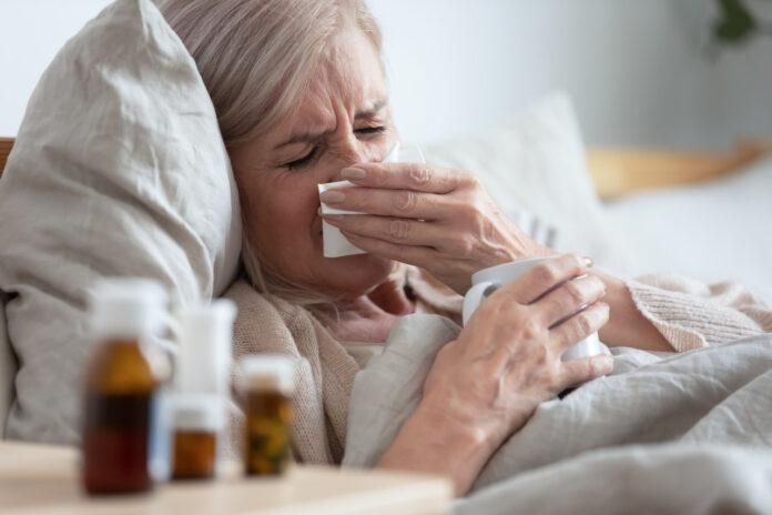 Przeziębienie - leżąca w łóżku starsza kobieta z katarem